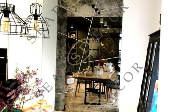 Состаренное бронзовое зеркало абстракционной формы на кухне