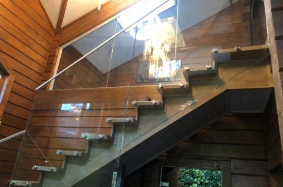 Стеклянное ограждение с поручнем на деревянной лестнице в частном доме